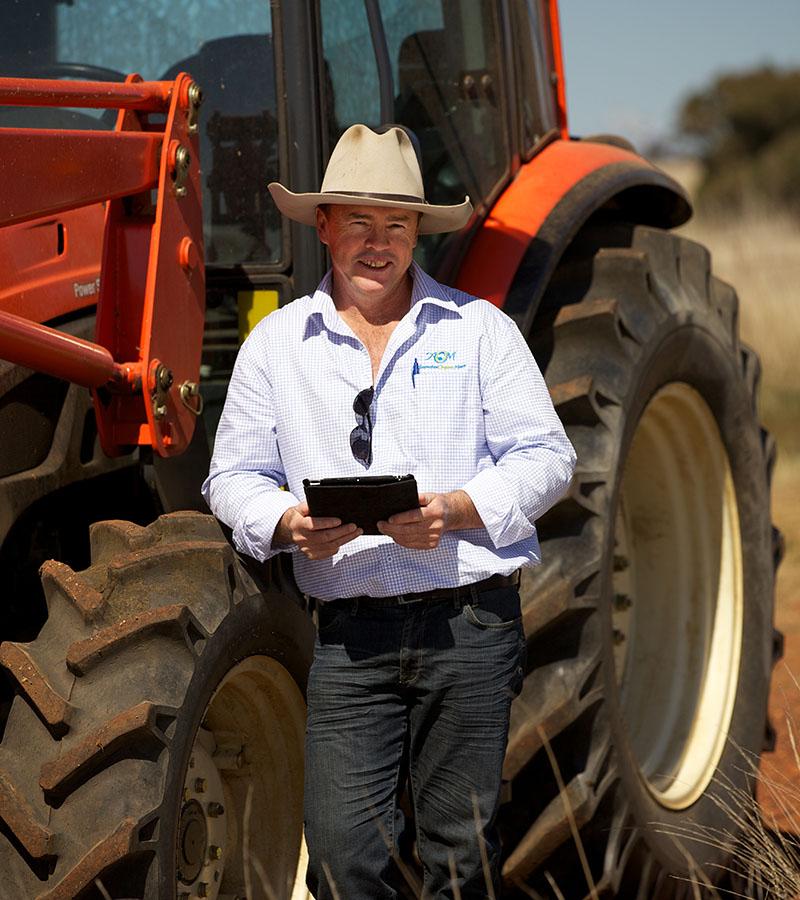 Matt O'Leary by a farm tractor