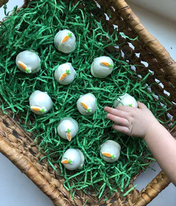 Hand grabbing Carrot Cake Balls in Easter Basket