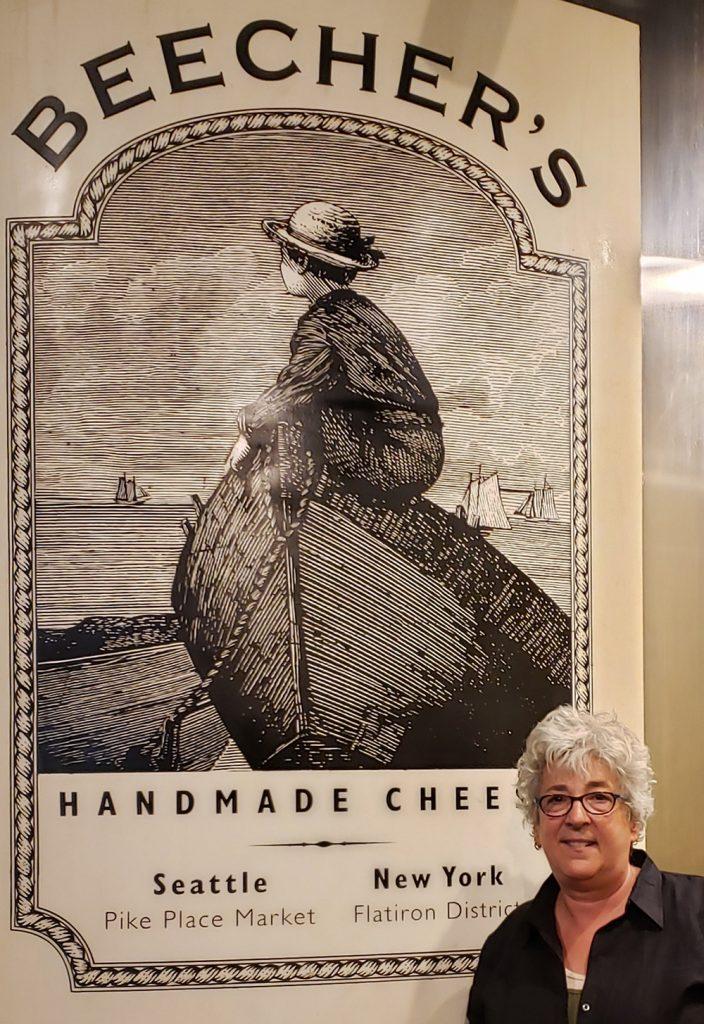 Heinen's cheese buyer Anne Somoroff standing in front of Beecher's Handmade Cheese sign