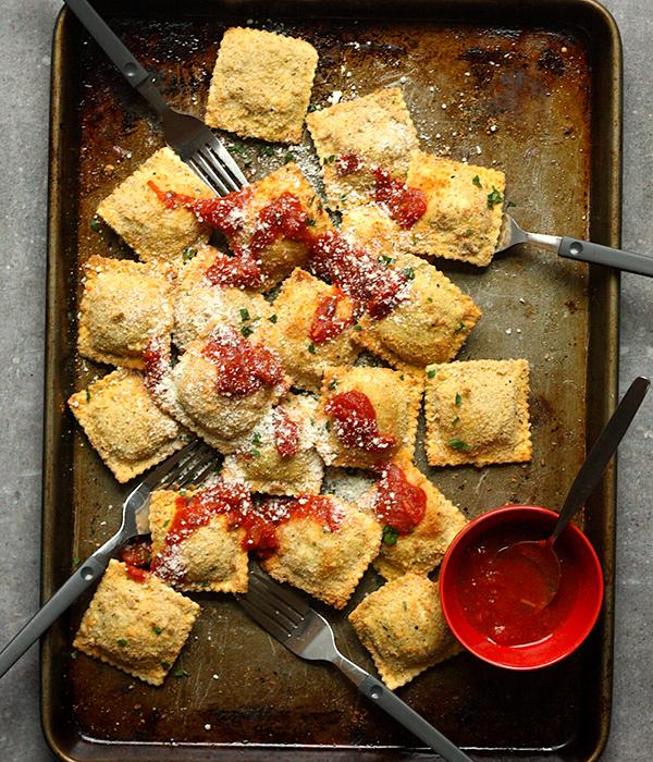 Toasted Chicken Parmesan Ravioli Bites on Baking Sheet with Marinara