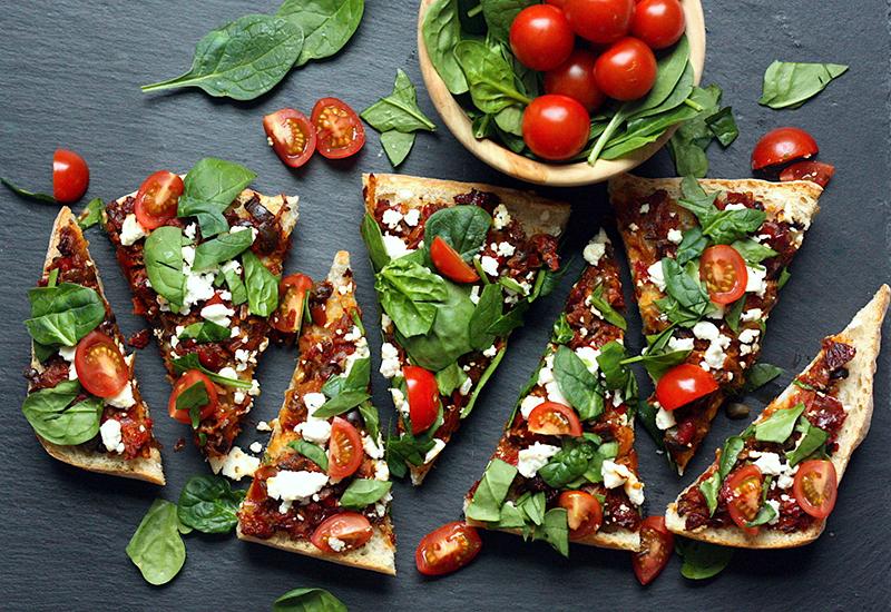 Mediterranean flatbread sliced into triangular pieces