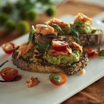 Smoked salmon avocado toast served on a white plate